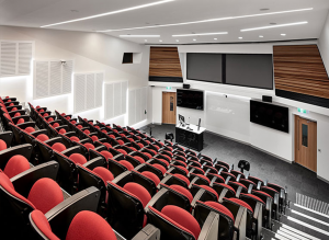 Lecture conference theatre with high tech audio visual fitout including LED display screens, speakers, lecture with gooseneck microphone, projector and projection screens