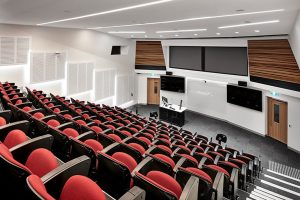 University Lecture Theatre conference room with high tech audio visual fitout including a lecturn with gooseneck microphone, LED displays, speakers and projection screens