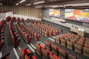 Lecture conference theatre with Projection screens, lecturn with gooseneck microphone, Speakers, and LED displays